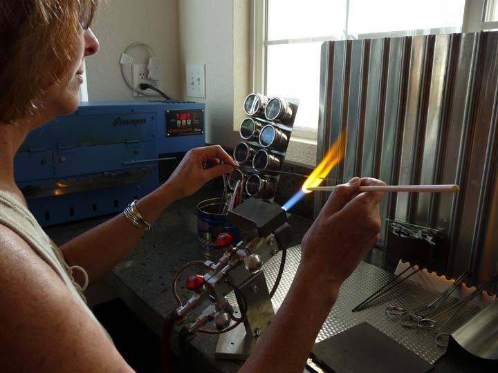 an image of Diana Dunn working in her studio with her torch